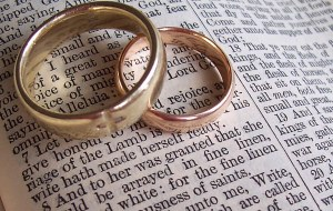 a-pair-of-wedding-rings-sit-on-an-open-bible-data